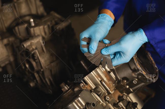 High angle view of bike mechanic repairing bike engine in garage