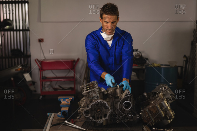 Front view of young Caucasian male bike mechanic repairing bike engine in garage