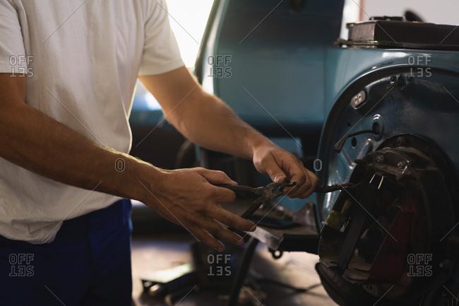 Mid section of Caucasian male bike mechanic repairing bike in garage