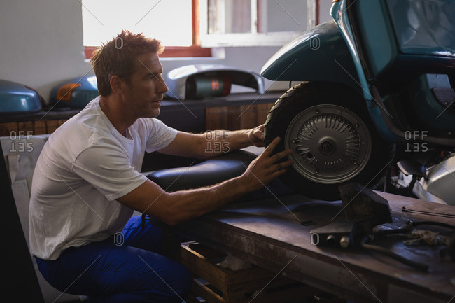 Side view of Caucasian male bike mechanic repairing motorbike tire in garage
