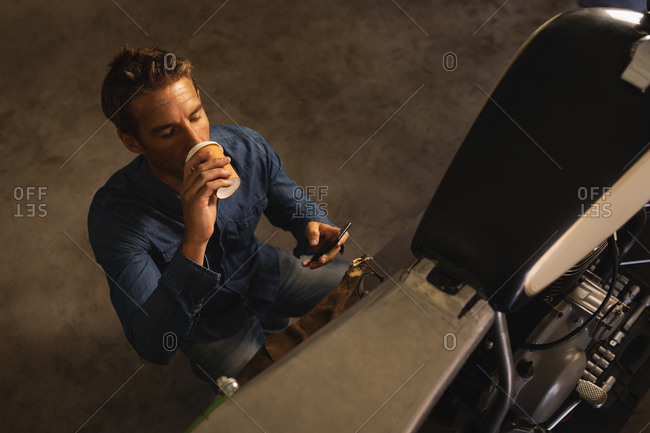 High angle view of Caucasian male bike mechanic drinking coffee while using mobile in garage