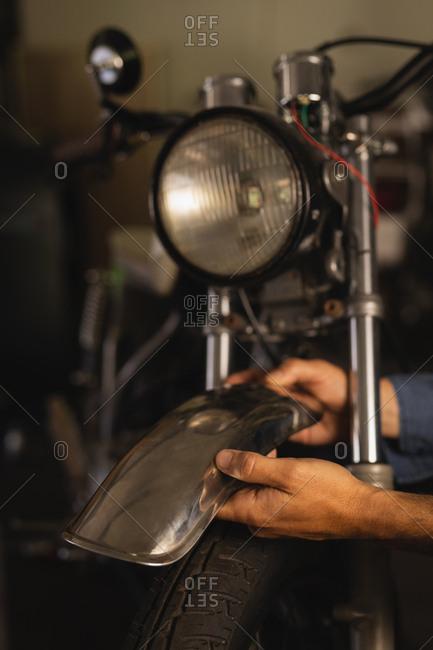 Caucasian male bike mechanic repairing mudguard of bike