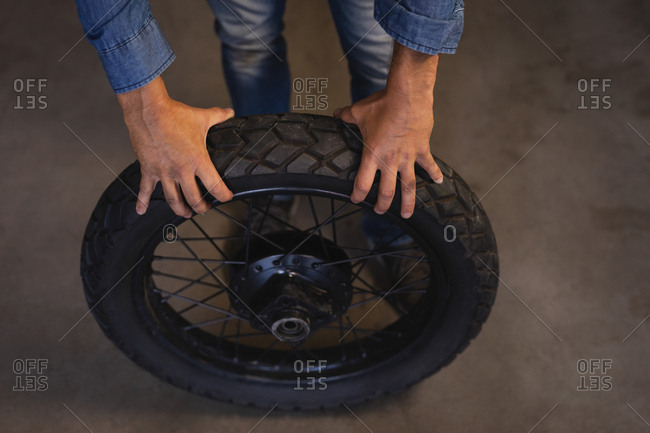 High angle view of bike mechanic holding tire while standing in garage