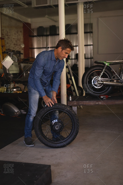 Side view of Caucasian male bike mechanic holding tire while standing in garage