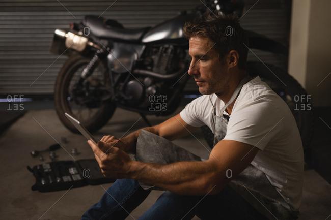 Side view of Caucasian male bike mechanic using digital tablet in garage