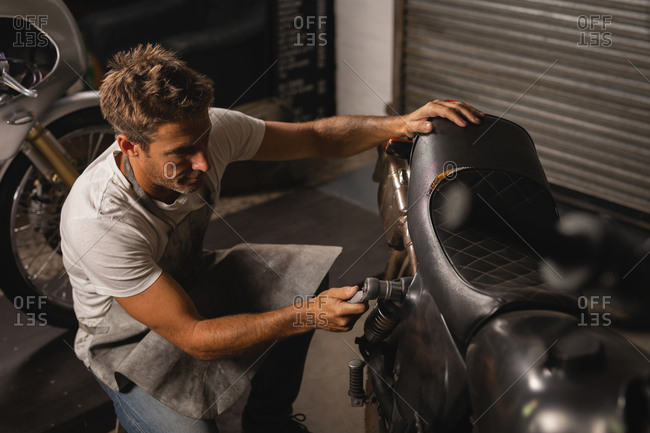 High angle view of Caucasian male bike mechanic checking bike with ratchet wrench in garage