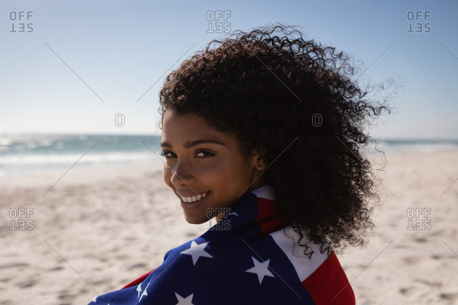 Portrait of beautiful young African American woman holding american flag while standing at beach on a sunny day