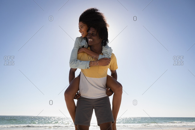 Front view of young African American man giving young African American woman piggyback at beach on a sunny day