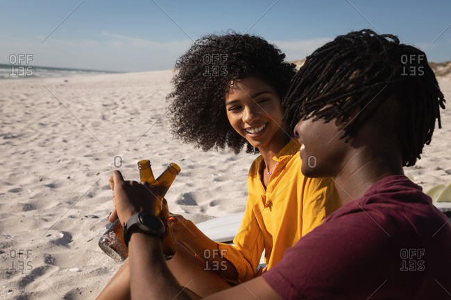 Side view of African American  couple toasting beer bottle at beach on sunny day