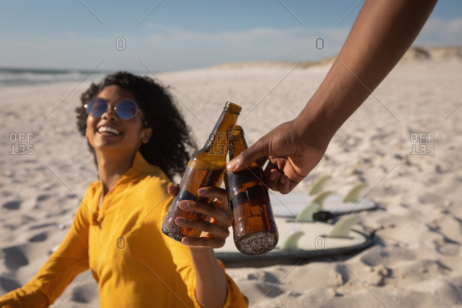 Side view of young African American couple toasting beer bottle at beach on sunny day
