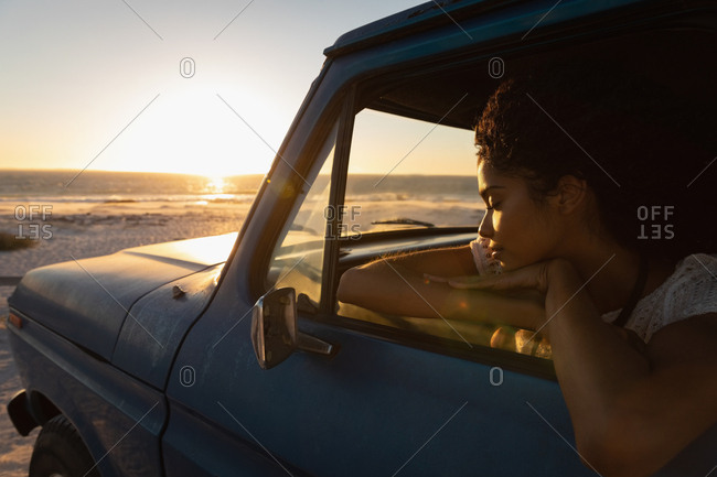 Side view of beautiful young African American woman dreaming while sitting in car at beach on sunset