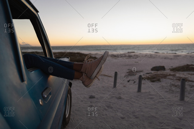 Low section of woman relaxing with feet up in a car on the beach at sunset