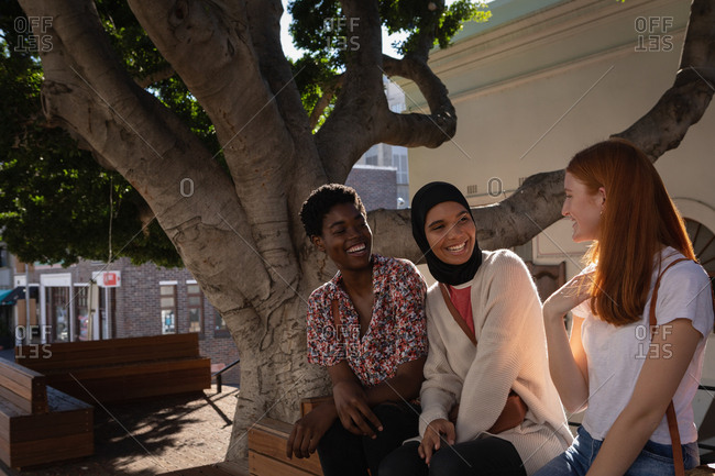 Side view of happy mixed race female friends interacting with each other while sitting under the tree