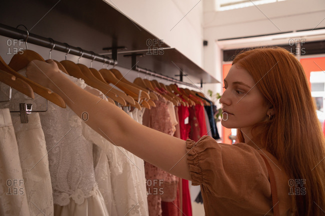 Side view of beautiful young Caucasian woman choosing dress in boutique