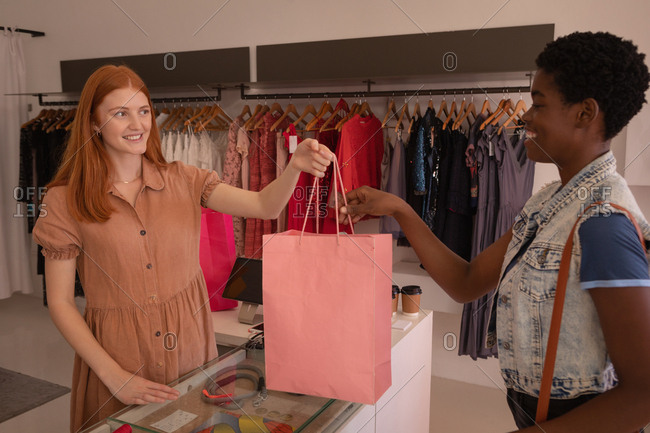 Side view of young Caucasian female store owner handling bag to young African American female customer at boutique