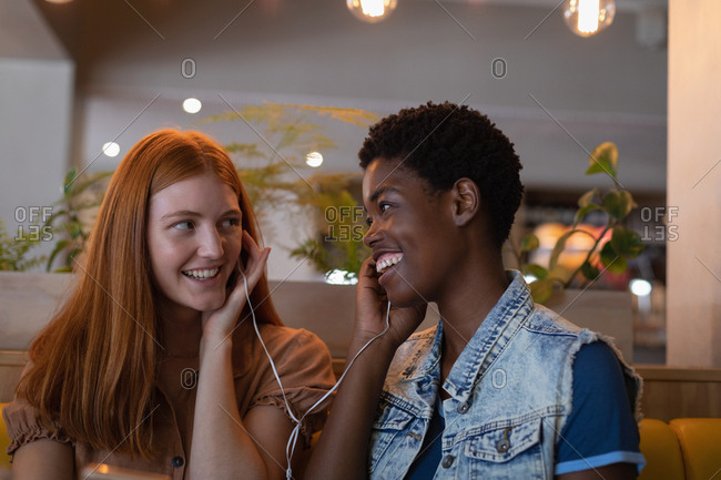 Front view of mixed race female friends listening music with ear phone at restaurant