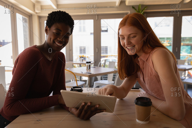 Side view of young mixed race female friends using digital tablet in a cafe