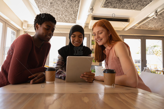 Front view of young mixed race female friends interacting with each other while using digital tablet in a cafe