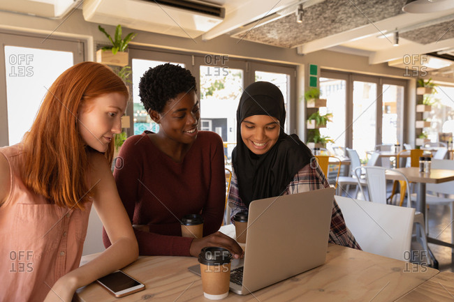 Side view of young mixed race female friends interacting with each other while using laptop in a cafe