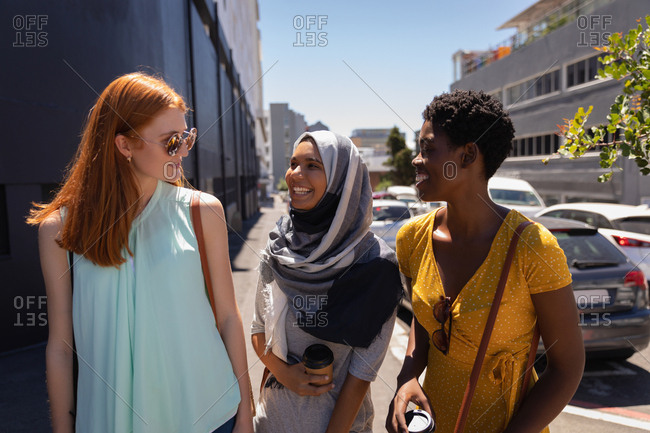 Front view of young mixed race female friends interacting with each other in the city street on sunny day