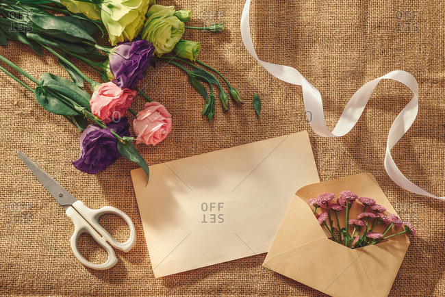 Lisianthus flowers and empty card with envelope on table.