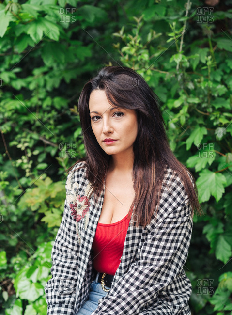 Young Brunette Woman Standing On The Park With Red And Plaid Clothes.