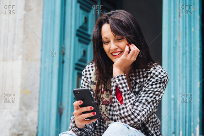 Young Brunette Woman With Red And Plaid Clothes Sitting In Front Of An Old Building With A Blueish Door While Using Her Phone.