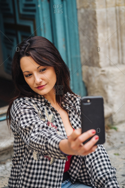 Young Brunette Woman With Red And Plaid Clothes Sitting In Front Of An Old Building With A Blueish Door While Taking A Selfie With Her Smartphone.