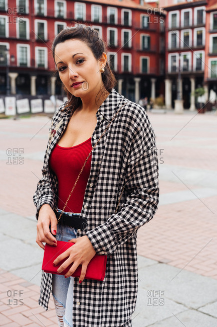 Young Brunette Woman With Red And Plaid Clothes Standing In Front Of Old Buildings In The Main Square Of A Spanish Town.