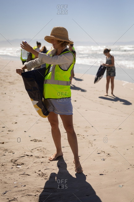Front side of young Caucasian female volunteer cleaning beach on a sunny day