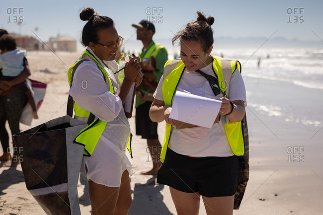 Front view of happy multi ethnic female volunteers discussing over clipboard while the other volunteer are cleaning on the beach