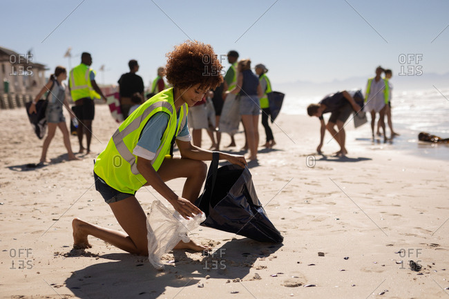 Side view of young mixed race female volunteer cleaning beach on a sunny day