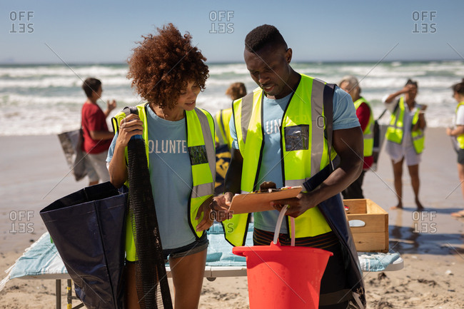 Front view of multi ethnic volunteers discussing over clipboard at beach on a sunny day