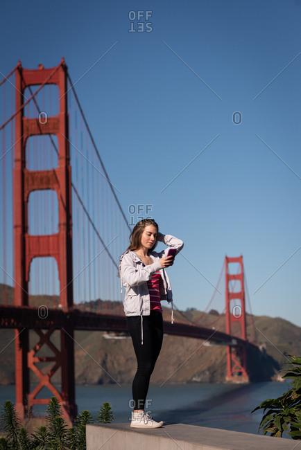 Side view of beautiful woman taking selfie near suspension bridge