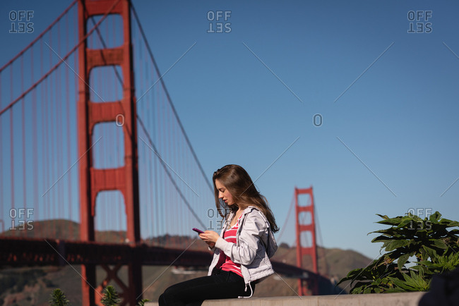 Side view of beautiful woman using mobile phone while sitting on sitting wall