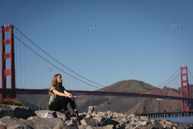 Front view of beautiful woman sitting on rock near golden gate bridge