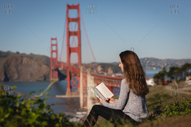 Side view of beautiful woman reading book while sitting on mountain slope