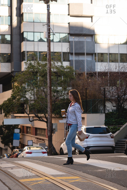 Side view of beautiful young Caucasian woman with coffee cup crossing the road in street in city