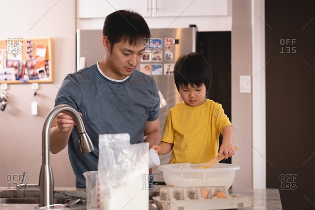 Front view of Asian father and son mixing dough together in kitchen at home