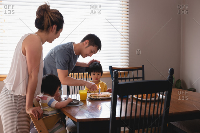 Side view of happy Asian father igniting candles on pancakes while having breakfast with his family at dining table
