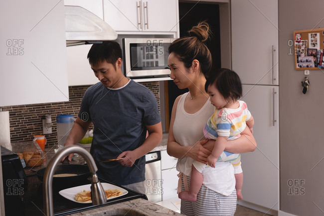 Side view of Asian mother and son looking at Asian father while making pancakes in kitchen at home