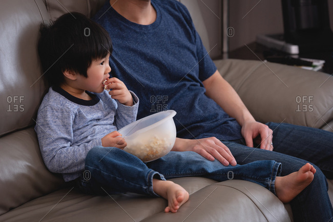 Front view of a happy Asian father and son sitting on sofa and eating popcorn while watching TV at home