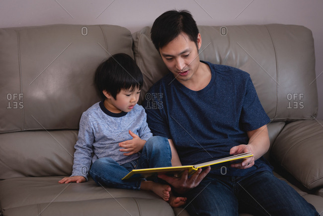 Front view of Asian father reading story book to his son while sitting on sofa at home