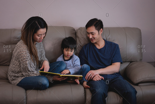 Front view of happy Asian family reading book while sitting together on sofa at home