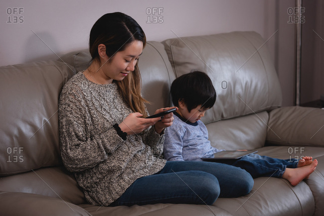 Side view of a happy young Asian mother using mobile phone while son using digital tablet on sofa at home