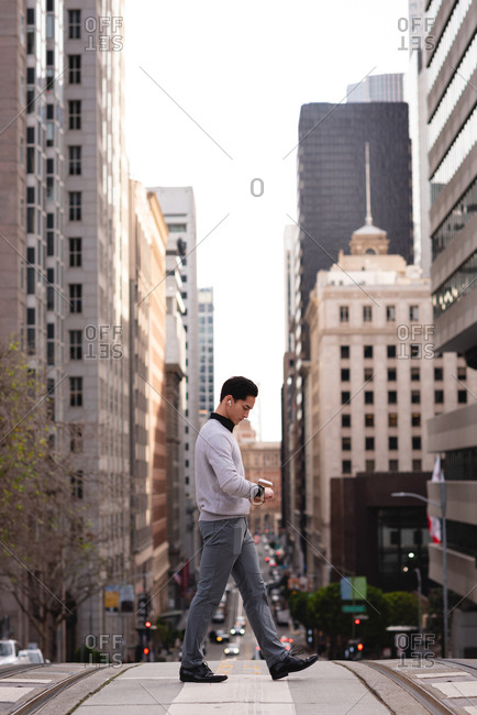 Side view of Asian man using smart watch and listening to music with wireless earphones while crossing the street
