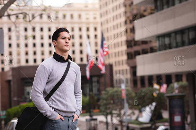 Front view of thoughtful Asian man standing on street