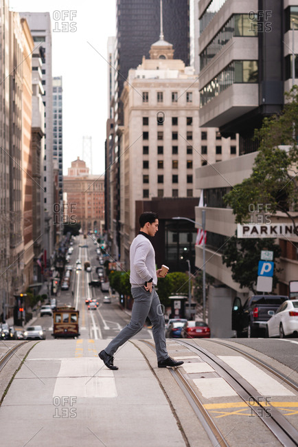 Side view of Asian man crossing the street while having coffee