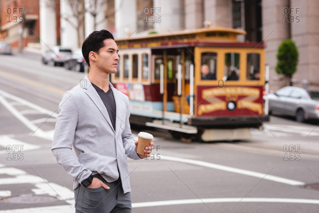 Front view of handsome Asian man standing on street while having coffee