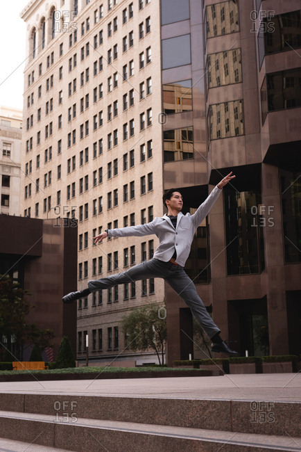 Front view of handsome Asian man jumping and dancing on stairs